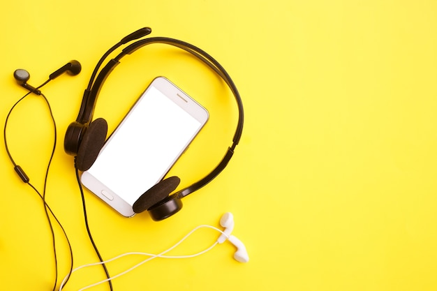 Headphones and smartphone on a yellow table. clubhouse social media concept. mock up, copy space, flat lay, top view