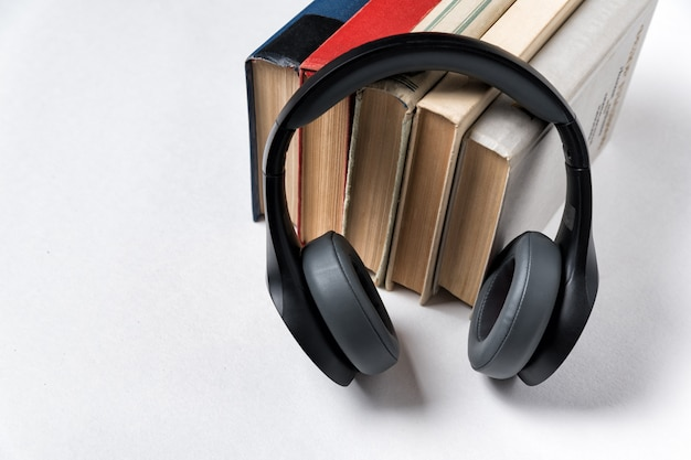 Headphones and a stack of books on white surface. audio library audio books concept.