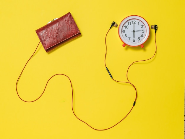 Headphones sticking out of the wallet and a red alarm clock. the concept of lifting the tone in the morning.