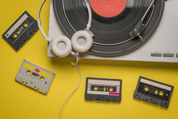 Headphones, a vinyl record player, and tape cassettes on yellow. retro devices for storing and playing audio recordings.