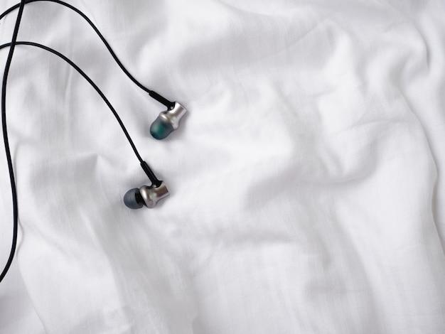 Headphones on white bed.