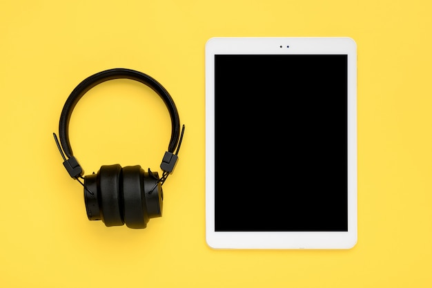 Headphones, white tablet with black screen isolated on yellow background