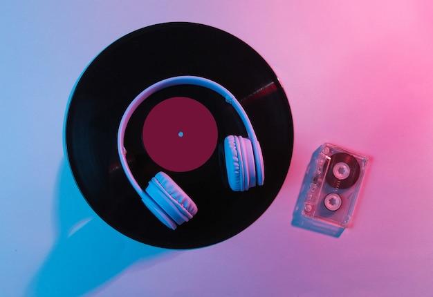 Наушники с аудиокассетой, виниловые пластинки. ретро волна, синий розовый неоновый свет, ультрафиолет. вид сверху, минимализм