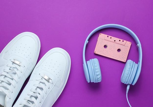 Наушники с аудиокассетой, белые кроссовки на фиолетовом фоне