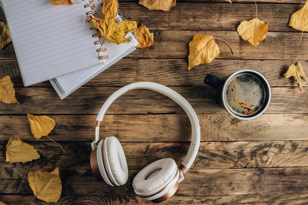 Headphones with autumn dry leaves and cup of coffee