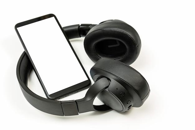 白い背景にbluetoothテクノロジーを搭載したヘッドフォン、音楽愛好家のためにペアリングされた黒い電話