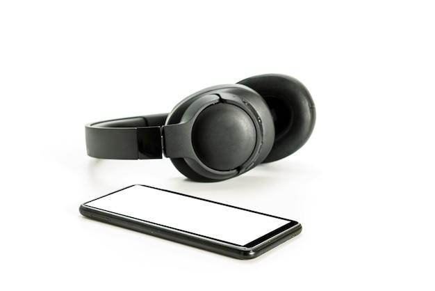 白い背景にbluetoothテクノロジーを搭載したヘッドフォン、音楽愛好家のためにペアリングされた黒い電話 Premium写真