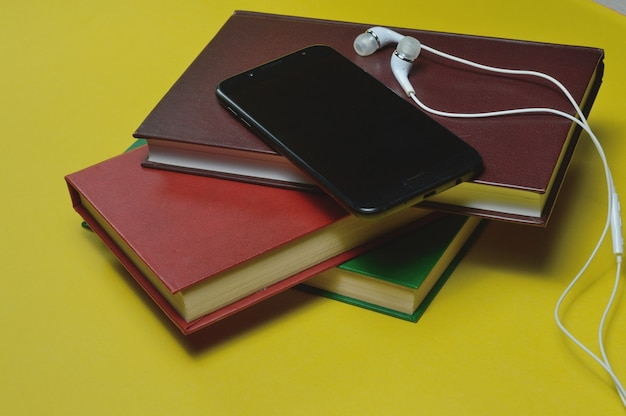 黄色の背景に本とスマートフォンが付いているヘッドフォン。