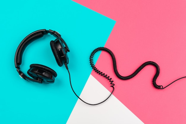 Headphones with cord on a bright color block background