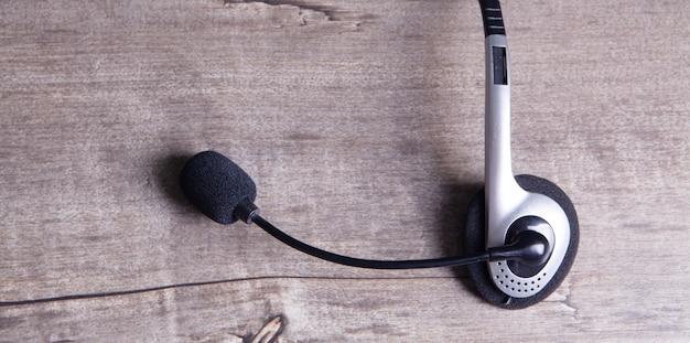 Наушники с микрофоном на деревянном фоне