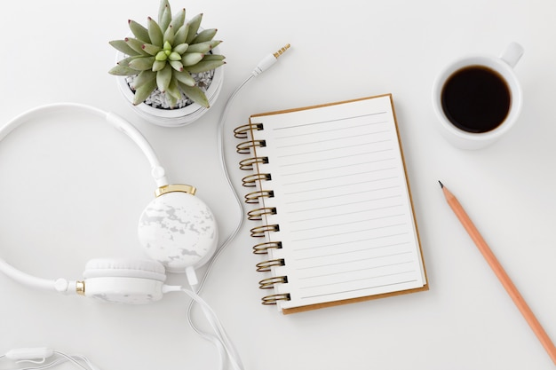Headphones with notebook on white desk
