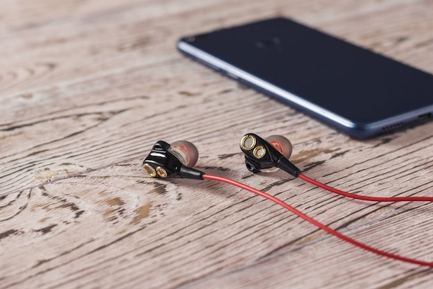 Headphones with red cord and a blue tinted smartphone on a wooden table