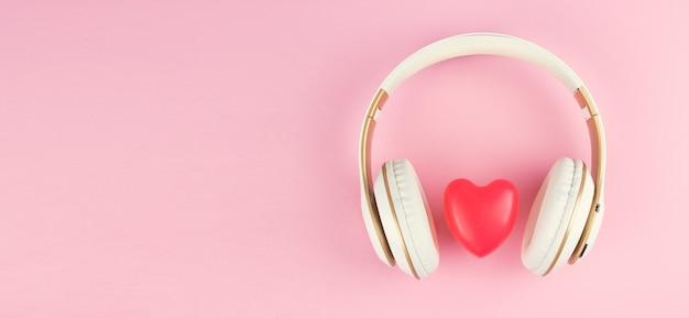 Headphones with red heart sign on pink background.