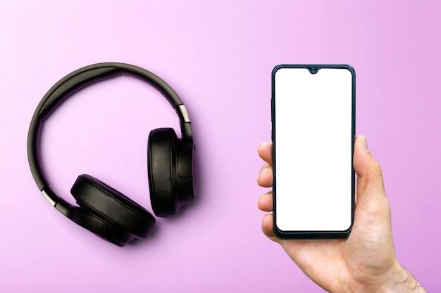 스마트폰이 있는 헤드폰을 조롱합니다. 빈 스마트폰 화면이 있는 컬러 네온 배경의 사운드 오디오 헤드폰. 음악 앱, 팟캐스트 및 오디오북 개념 듣기. 고품질 사진