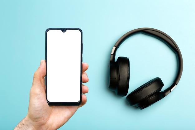 스마트폰이 있는 헤드폰은 빈 색상의 네온 배경에 사운드 오디오 헤드폰을 조롱합니다.