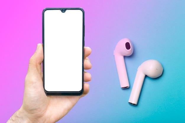 스마트폰이 있는 헤드폰은 컬러 네온 배경에서 사운드 오디오 헤드폰을 조롱합니다.
