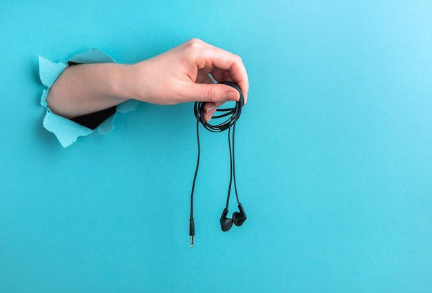 Headphones in a woman's hand on a blue background with a hole