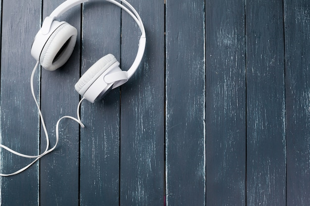 Headphones on wooden desk table background