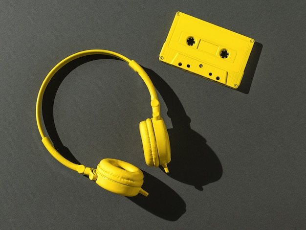 Headphones and a yellow cassette with a magnetic tape on a black background in bright light. color trend. flat lay.