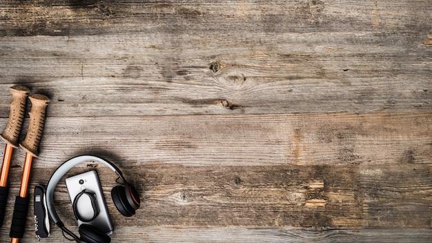 トレッキングポール、携帯電話、木製の背景にheadpnones