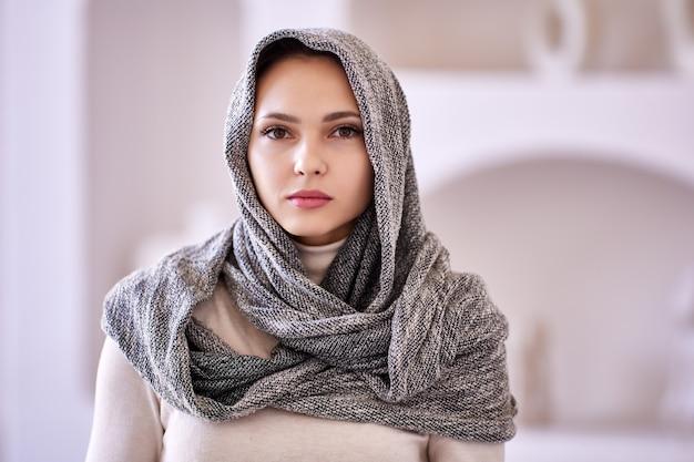 집에 서 있는 이슬람 여성의 머리에 스카프