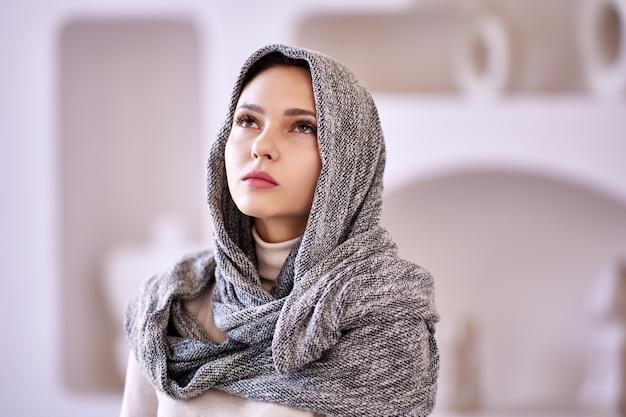 실내에 서 있는 이슬람 여성의 머리에 스카프