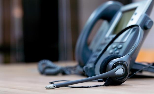 カスタマーサービスサポートの概念のためのオフィスの机に電話装置を備えたヘッドセット