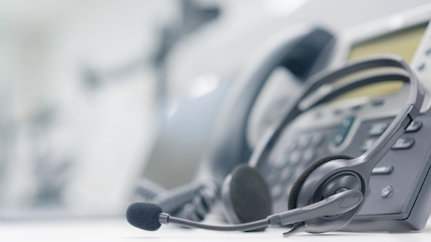 カスタマーサービス用のオフィスデスクに電話デバイスを備えたヘッドセット