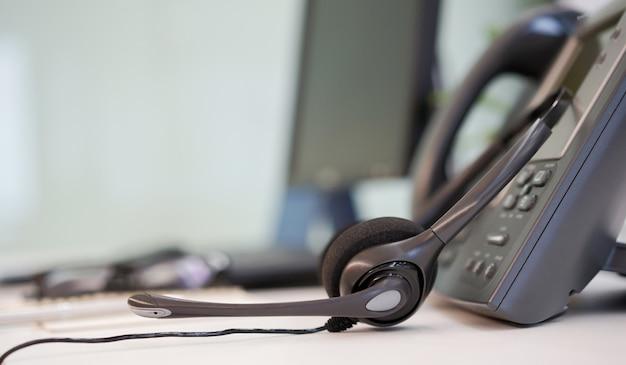 オフィスの机に電話装置付きヘッドセット