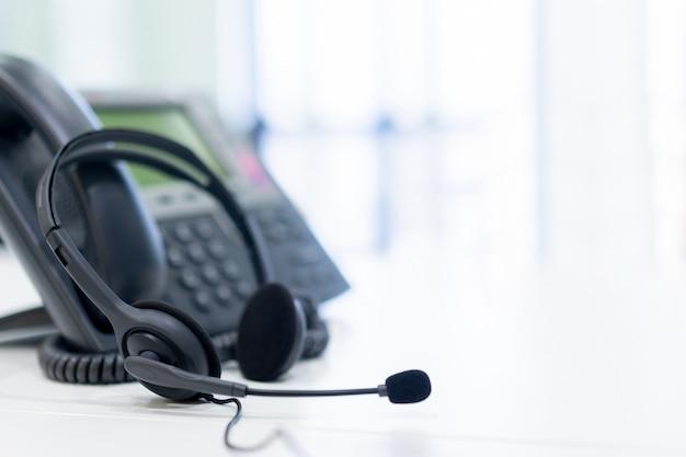 オフィスの机で電話デバイスとヘッドセット