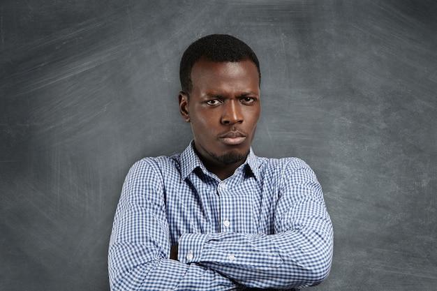 Primo piano del volto dell'insegnante africano serio arrabbiato con le braccia conserte, insoddisfatto dei suoi studenti che si comportano male, in piedi contro la lavagna vuota con lo spazio della copia per il testo o il contenuto pubblicitario