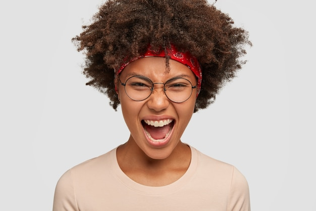 Headshot of annoyed displeased afro american girl has outraged facial expression