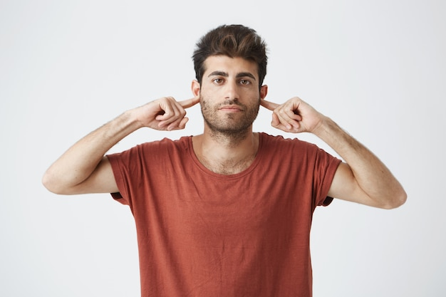 Headshot of annoyed stylish italian guy in red t shirt looking grumpy, closing ears with fingers showing disrespect on his friend words.