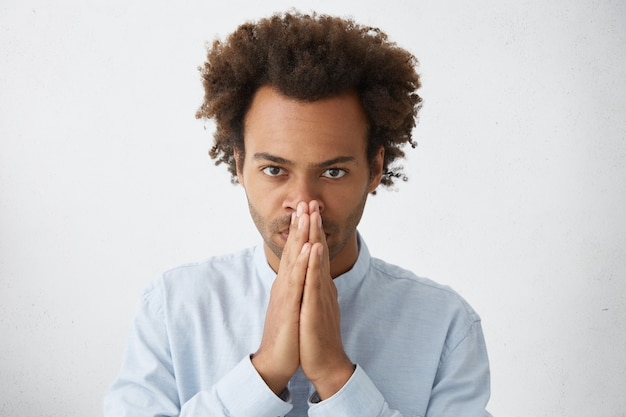 Headshot of attractive afro american employee with funky hairstyle holding hands at his face