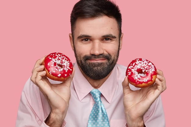 Il colpo alla testa del maschio barbuto attraente ha un'espressione amichevole, un sorriso gentile, setole spesse, indossa camicia e cravatta, tiene gustose ciambelle in entrambe le mani