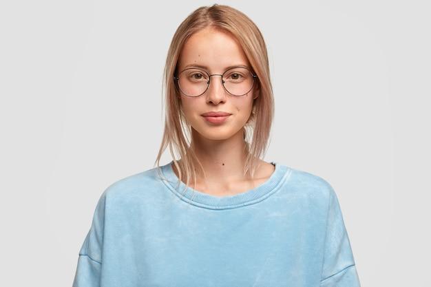 Headshot di attraente femmina caucasica guarda direttamente la fotocamera