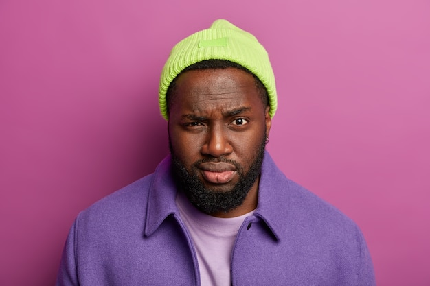 Headshot of attractive serious man with dark skin, full lips, looks mysteriously at camera, wears green hat and purple coat, stands indoor