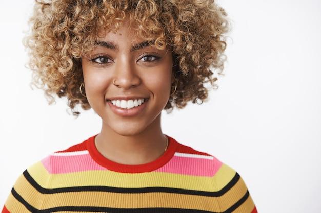 Colpo in testa di giovane donna dalla carnagione scura attraente e dall'aspetto amichevole dall'aspetto gioioso con un taglio di capelli riccio equo in maglione a righe sorridente felice e ottimista alla macchina fotografica sul muro bianco