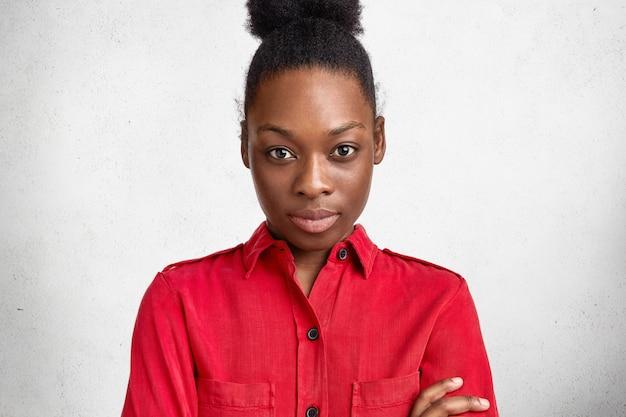 Headshot di attraente giovane modello femminile con acconciatura afro e pelle scura, indossa una camicetta rossa, sicuro nella sua correttezza, pone su sfondo bianco di cemento. persone, etnia, concetto di bellezza