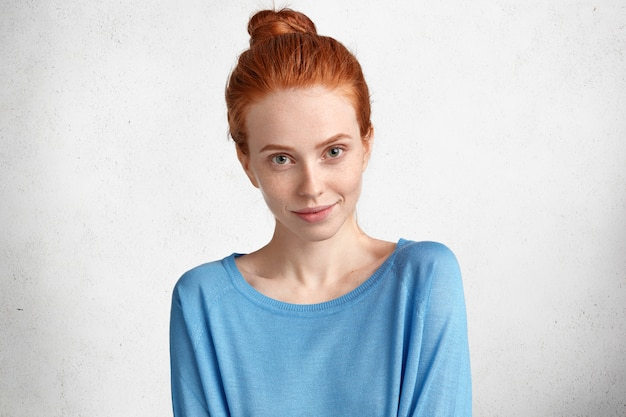 Headshot of attractive young red haired female with hair knot, has pleased look, dressed in casual blue sweater, going to meet with best friend after work