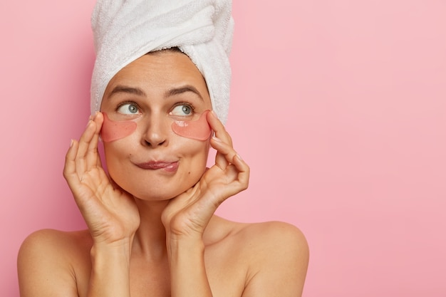 Headshot of attractive young woman applies hydrogel patches under eyes, bites lower lip, removes dark circles, looks aside, stands naked against pink wall. skin care and beauty concept.