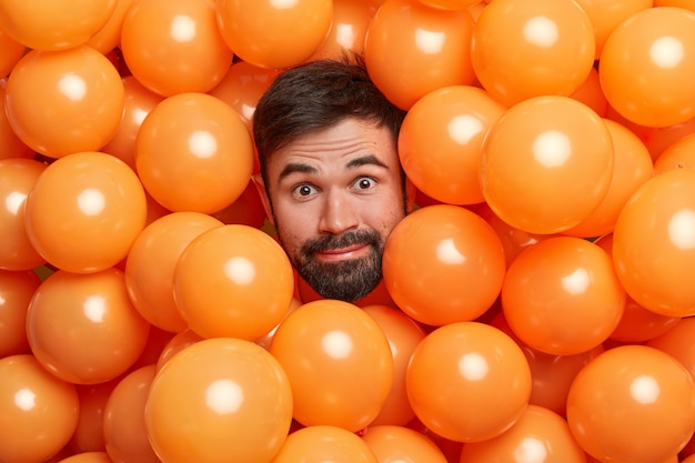 Headshot of bearded adult european man surrounded with inflated orange balloons prepares for party