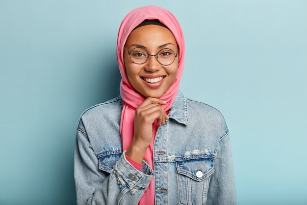 Headshot of beautiful arabian woman with toothy smile, holds chin, wears round spectacles, wears special traditional clothes