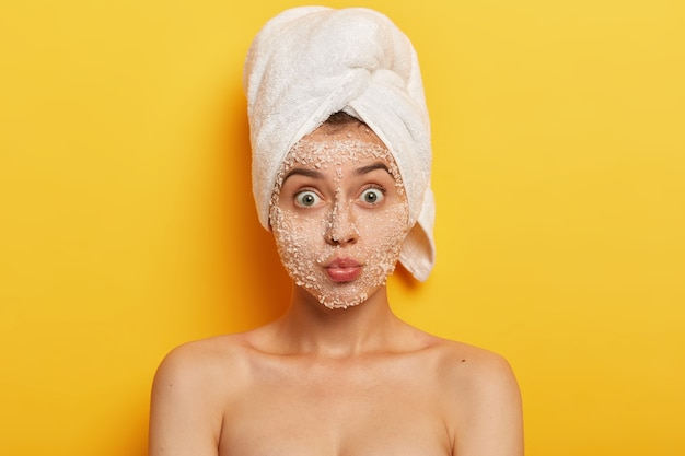 Headshot of beautiful caucasian woman has widely opened eyes, keeps lips folded, cares about purity and freshness of skin, has surprised face expression, well cared body, takes shower in bathroom