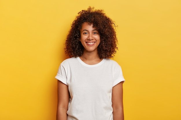 Headshot of beautiful dark skinned curly has pleased expression, rejoices success, enjoys spare time, wears casual t shirt, isolated on yellow wall. people, positive emotions, feelings concept