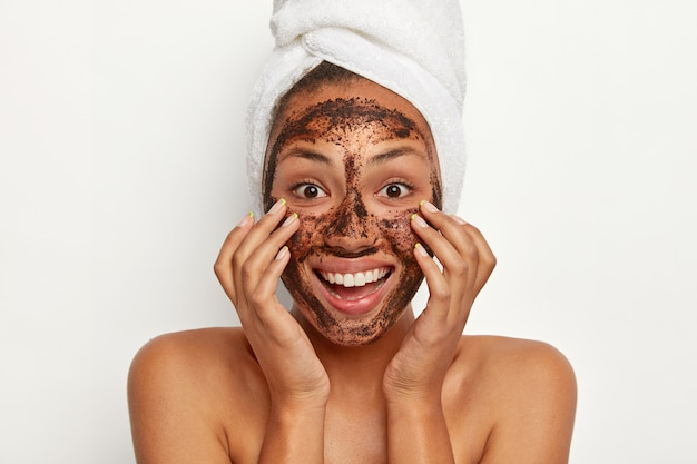 Headshot of beautiful dark skinned woman wears coffee scrub facial mask, keeps hands on cheeks, smiles broadly, wears white towel on head, models indoor against white wall. face treatment