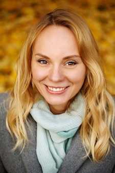 Headshot of beautiful female with blonde long hair and pretty smile and brown eyes autumn time Premium Photo