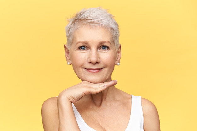 Headshot of beautiful middle aged woman with stylish pixie hairdo placing palm under chin, looking at camera with cute confident smile, making gesture