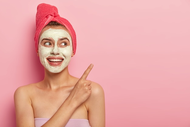 Headshot of beautiful relaxed female model points index finger on copy space, applies natural clay mask on problematic skin, reducess dryness