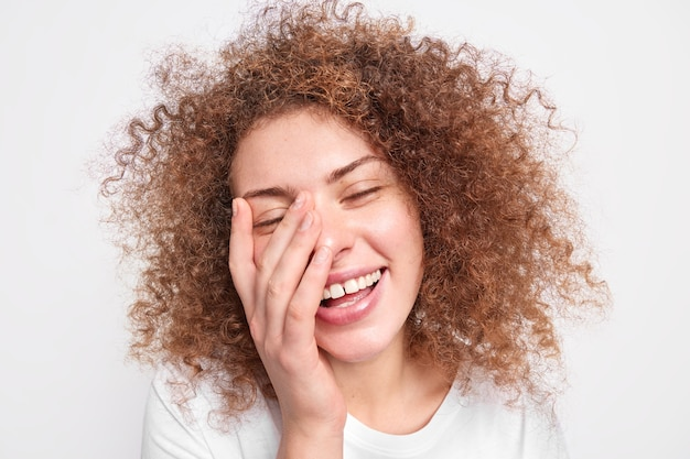Headshot of beautiful sincere european woman with curly bushy hair has fun laughs out covers face with palms smiles broadly expresses happiness isolated over white wall. positive emotions